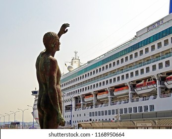 Bronze statue of a man in front of the cruise ship 'Aurora' on the quay of transatlantic ships of the port of Coruna Coruna, Galicia, Spain 08/21/2018