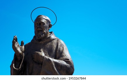 bronze statue of Padre Pio with blue sky in the background