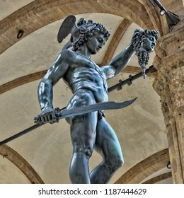 Bronze statue of Perseus with the Head of Medusa. The mythical Greek hero holding up the severed head of Medusa. Ancient sculptures in Florence, Italy - April 17, 2018