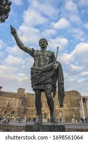 Bronze statue of the Roman Emperor Augustus on Via dei Fori Imperiali in front of old brick buildings near the Roman Forum, Rome, Italy.