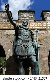 Bronze statue of Roman emperor standing in front of the reconstructed south gate of the Roman fortress called Saalburg, north of Frankfurt, Germany.