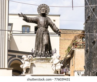 A bronze statue of San Gaetano in the busy streets of the city of Naples, Italy. It has been recently restaured