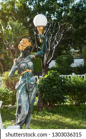 bronze statue of a woman in the Park in the hand street lamp in the form of a ball