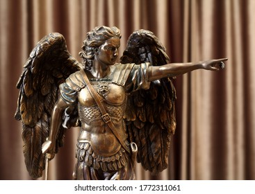 A bronze statuette of the Archangel Michael points a finger forward.