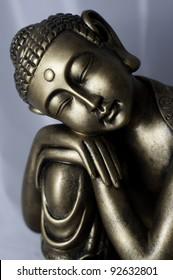 A bronze thai buddha sculpture on a white background