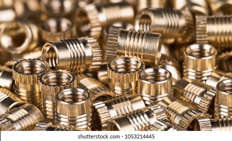 Bronze threaded inserts as background. Close-up of decorative pile from golden metal parts. Idea of construction, build, store or mechanical engineering. Great depth of field.