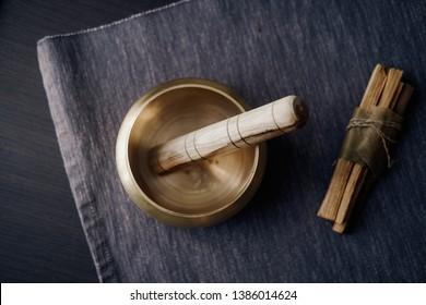 Bronze tibetan singing bowl with wooden stick, palo santo wood. Sound healing, sound bath therapy