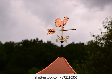Bronze Weathervane Against a Cloudy Sky