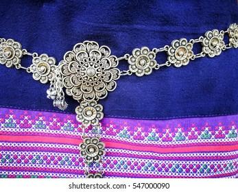 Bronze woman belt on Thai cotton cloth texture background
