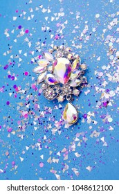 Brooch with colored crystals in spangles isolated on blue background