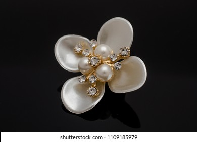 Brooch flower with pearls isolated on black