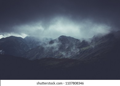 Brooding atmospheric mountainous landscape with dark ominous storm clouds obscuring high rugged mountain peaks in a weather concept