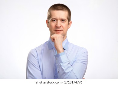 a brooding successful man makes a decision, pondering, holding his hand at the chin, in a blue light casual shirt, looking into the camera. Isolated, on white