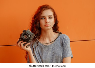 Broody Teen Girl With Vintage Camera In Hands