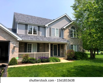 Brookfield, WI / USA - July 29, 2019: Grey house in summer gets new siding, gutters, roof shingles and landscaping. At home.