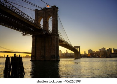 Brooklyn Bridge across the East River in New York City at sunset.