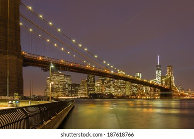 Brooklyn bridge from the beginning at Brooklyn Heights to the end in downtonwn Manhattan at night with reflections of lights in the water