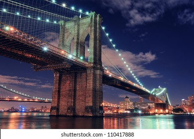 Brooklyn Bridge closeup over East River at night in New York City Manhattan with lights and reflections.