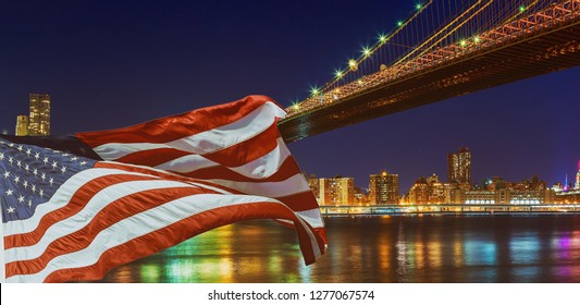 Brooklyn Bridge closeup over East River at night in New York City Manhattan and American flag flying