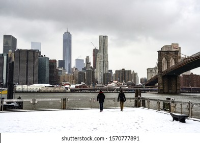 Brooklyn Bridge during winter snowstorm blizzard in New York City with heavy snow falling, cars covered by snow and people commuting during snow storm. Manhattan, New York USA January 6, 2015
