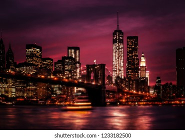 Brooklyn Bridge, East River and Manhattan at night with lights and reflections. New York City