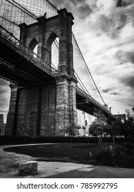 Brooklyn Bridge and grass field with cloudy sky in black and white