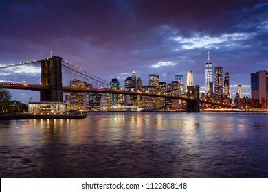 Brooklyn Bridge and illuminated Lower Manhattan skyscrapers at dusk with the East River. Manhattan, New York City