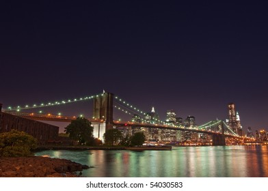 The Brooklyn Bridge lit up at night in front of the Manhattan skyline in New York City.