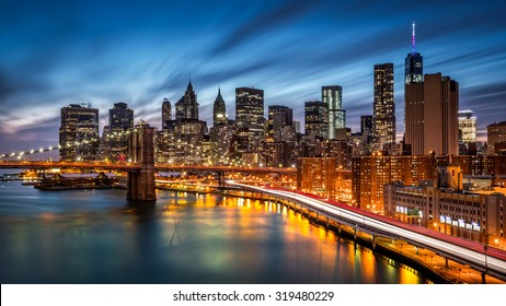 Brooklyn Bridge and the Lower Manhattan at dusk with rush hour traffic trails on FDR drive