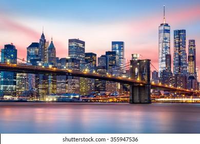Brooklyn Bridge at and the Lower Manhattan skyline under a purple sunset