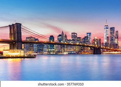 Brooklyn Bridge and the Lower Manhattan skyline under a purple sunset