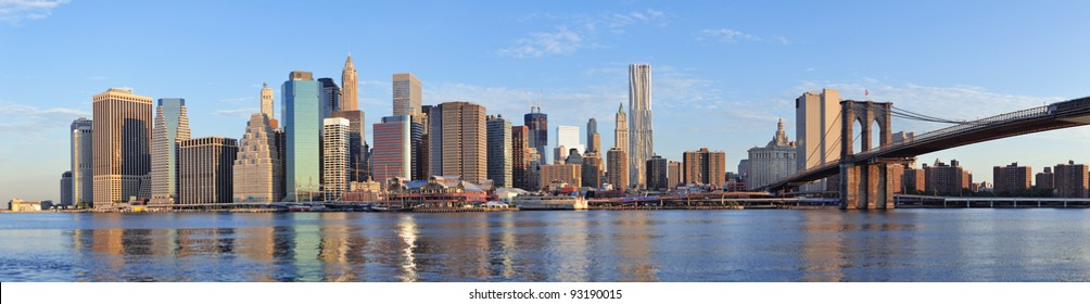Brooklyn Bridge with lower Manhattan skyline panorama in the morning with cloud and river reflection over East River in New York City