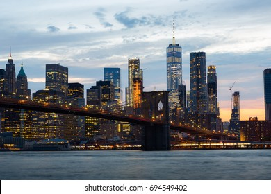 Brooklyn Bridge and lower manhattan skyscrapers at dust in New York City. Light from the city illuminated over the East river and one world trade center in the skyline.