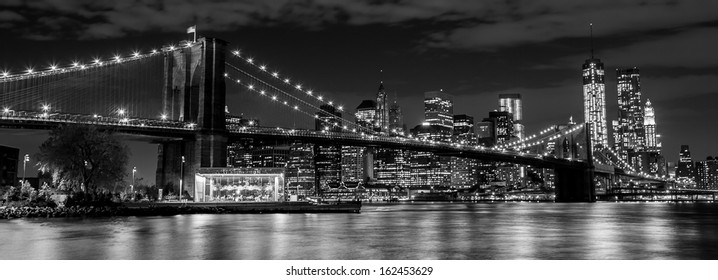 Brooklyn Bridge with Manhattan skyline in the background at night in black and white