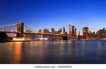 Brooklyn Bridge and New York City skyline illuminated at dusk with reflections in Eastern River, USA