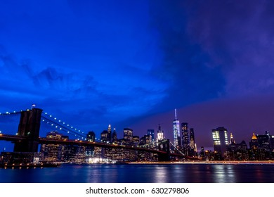 brooklyn bridge and new york city in the night time with cloudy sky