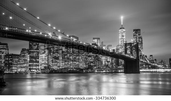 Бруклинский мост и Нью-Йорк Манхэттен в центре города в сумерках с небоскребами, освещенными над панорамой Ист-Ривер. Пространство для копирования. Черно-белое изображение.