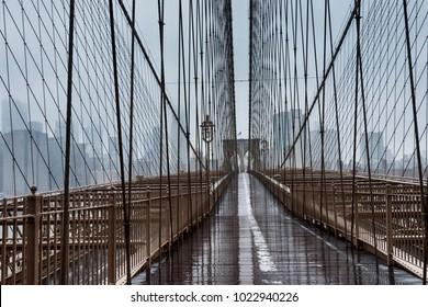 Brooklyn bridge in New York, empty on rainy day, with cityscape of Manhattan.