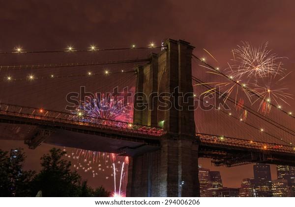 Brooklyn bridge in New York at night with fireworks, USA