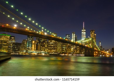 Brooklyn Bridge at night with water reflection, New York City Skyline, NY, USA
