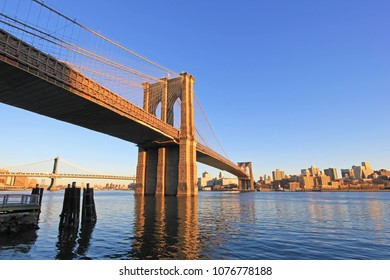 Brooklyn Bridge over East River with view of New York City Lower Manhattan, waterfront at twilight, USA