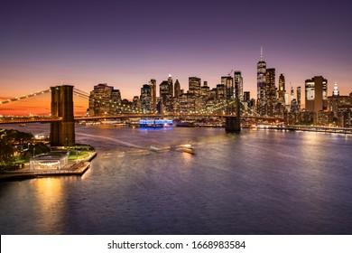 Brooklyn Bridge over the East River and the Manhattan downtown city skyline at night in New York USA