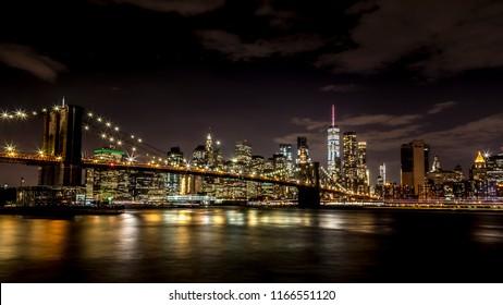Brooklyn Bridge with view to Manhattan Skyline by night