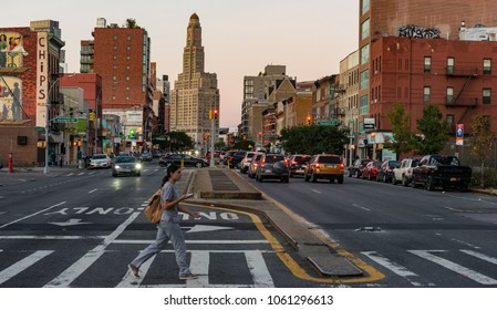 Brooklyn, New York - 3rd Oct, 2017: Woman walking on the crosswalk on 4th Ave in Brooklyn during sunset with the vintage New York architecture of williamsburgh savings bank tower in the background.