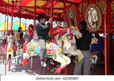 BROOKLYN, NEW YORK - APRIL 13, 2017: Children and adults ride Coney Island carousel in Luna Park at Coney Island Boardwalk in Brooklyn.