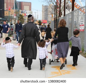 BROOKLYN, NEW YORK - APRIL 23, 2019: Jewish orthodox family enjoy outdoors during Passover at Coney Island in Brooklyn, New York