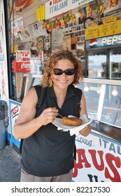 BROOKLYN, NEW YORK - JUL 18: A woman eating a knish at a restaurant on Coney Island boardwalk a popular beach and tourist area on the Atlantic Ocean in southern Brooklyn New York, July 18, 2010.