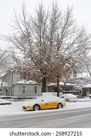 BROOKLYN, NEW YORK - MARCH 5, 2015: New York Yellow taxi under snow in Brooklyn, NY during massive Winter Storm Thor