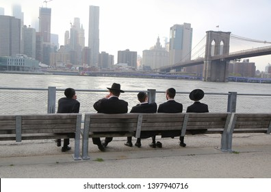 BROOKLYN, NEW YORK - MAY 2, 2019: Jewish orthodox teenagers enjoy outdoors near Brooklyn Bridge in New York