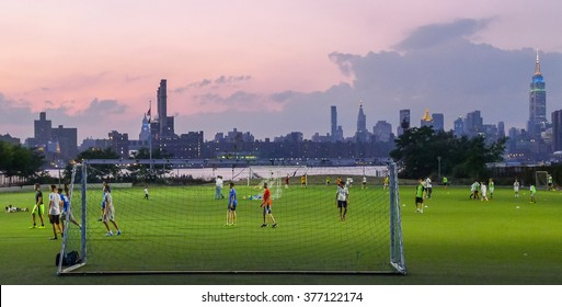 Brooklyn, New York - September 05 2014: Panoramic view at Manhattan with soccer team on grass field.